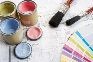 Puszki z farbą, pędzle, plany budowlane